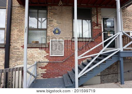 CADILLAC, MICHIGAN / UNITED STATES - MAY 31, 2017:  A stairway leads to the back door of an historic brick building, in downtown Cadillac, leads to the Cadillac Masonic Center and various businesses.