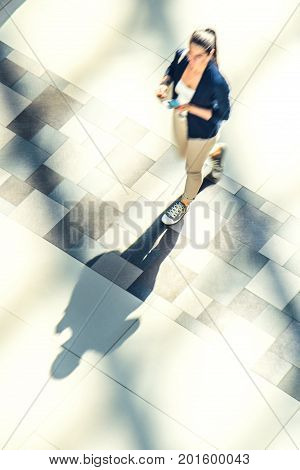 Silhouette of a walking woman with long shadow in a public building hall top view . Abstract background of blur in motion figure of a girl from above. Low speed shutter shot.