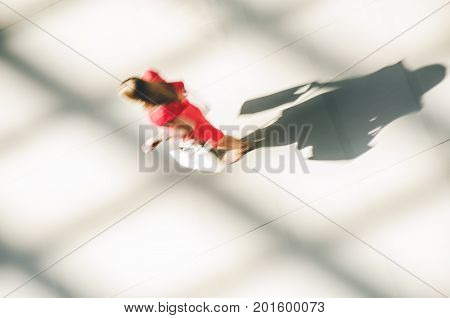 Silhouette of a walking woman with long shadow from above. Abstract background of blur in motion figure of a yang woman in red dress in a public building hall. Shopping concept