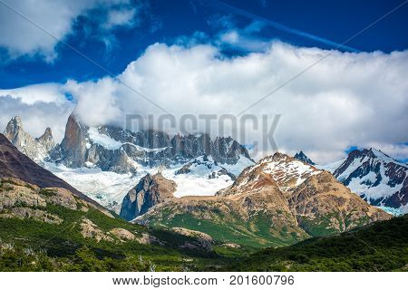 Green valley and mountains in the snow. Landscape of mountains with clouds in the afternoon. Snow-capped mountain tops are shrouded in clouds. Sunlight highlights the snowy peaks of the mountains.