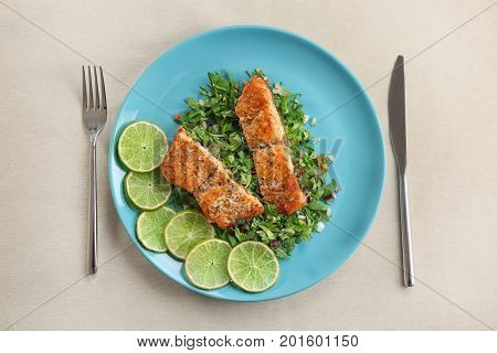 Plate with delicious salmon, sliced lime, herbs and flatware on light table