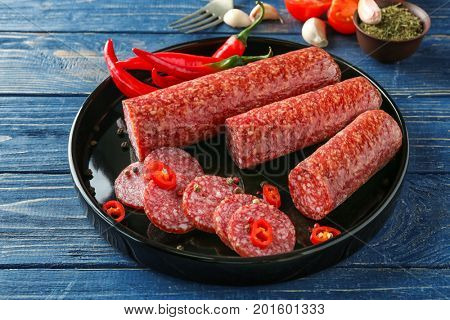 Plate with delicious sliced sausage and chili pepper on table