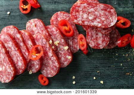 Delicious sliced sausage and chili pepper, closeup