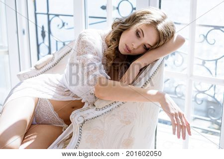 Beautiful sexy lady in elegant white robe. Close up fashion portrait of model indoors. Beauty blonde woman. Attractive female body in lace lingerie. Closeup fashionable naked girl in underwear