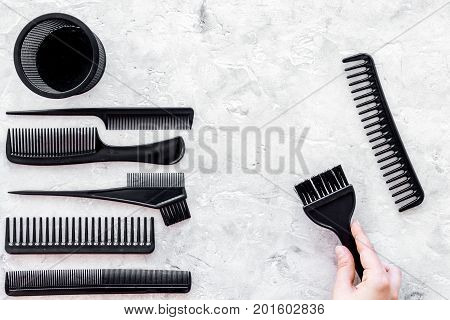 beauty salon black work tools with comb for hair dress and coloring on stone desk background top view