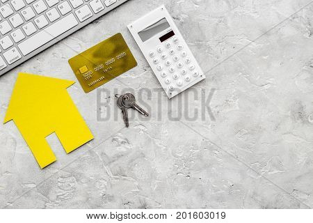 work desk with keyboard, keys and paper house figures for selling house set stone background top view space for text