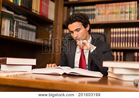 Man reading a lot of books in his office
