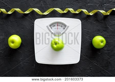 Lose weight concept. Bathroom scale, measuring tape, apples on black background top view.