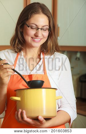 Housewife making soup meal dinner. Middle aged woman holding spoon ladle and pot. Housekeeper wearing orange apron preparing food.