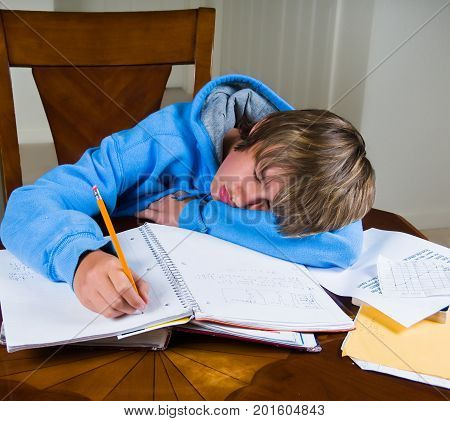 A young teenage boy falls asleep while doing a stack of homework from school.