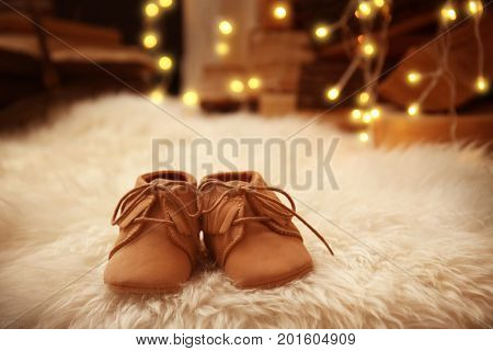 Baby booties on fluffy carpet. Christmas concept