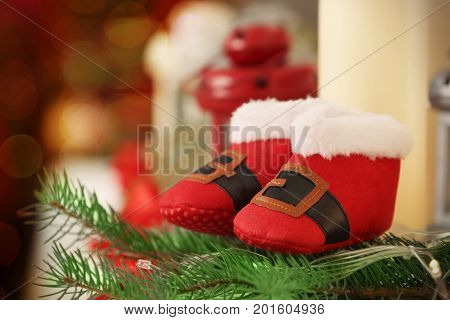 Christmas baby booties on blurred background