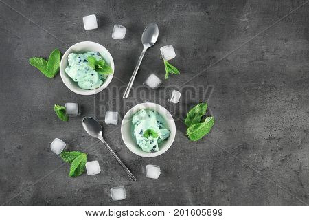 Composition with delicious mint chocolate chip ice cream and ice cubes on grey table