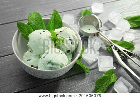 Composition with delicious mint chocolate chip ice cream and ice cubes on wooden table