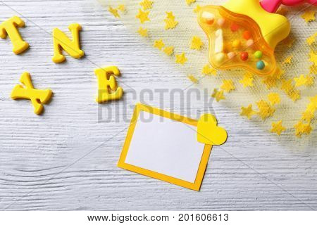 Greeting card with rattle on wooden background