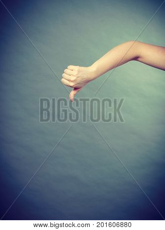 Bad negative emotions and feelings concept. Female hand showing thumb down. Depressed dissatisfied woman making hand gesture