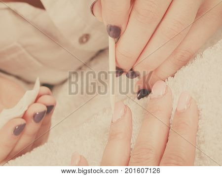 Nail care beauty wellness spa treatment concept. Woman beautician preparing nails before manicure pushing back cuticles using wooden stick