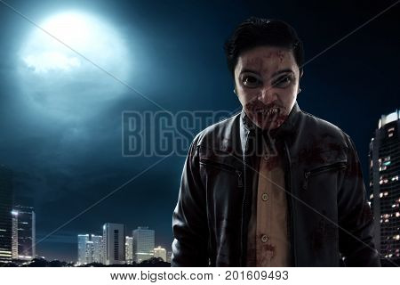 Angry vampire standing on city building at night