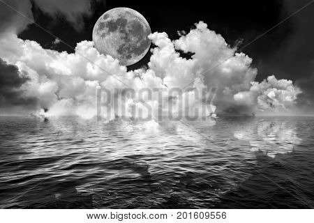Full moon and clouds in dark fantasy night sky reflected in wavy ocean water