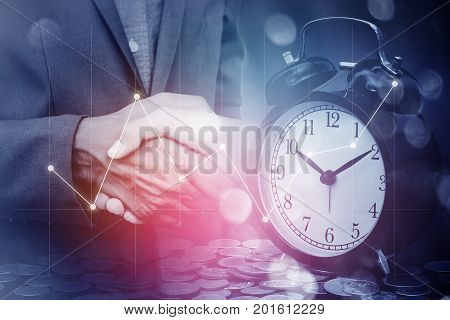 Double exposure of business man handshake with a row of stack money coins and analog clock with business graph information diagram concept for business finances and saving money.