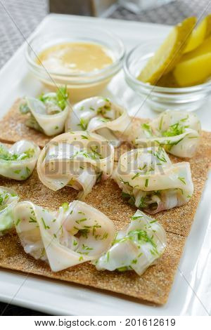 Crisp bread with lard garnished with pickled cucumber and sauce
