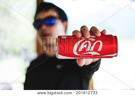 THAILAND - 9 AUG - Asian guy showing Coca-Cola can in Pattaya, Thailand on August 9,2017