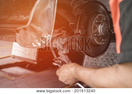Car Lifted In Automobile Service For Fixing, Repair, Changing Brake Disc In Garage, Close Up