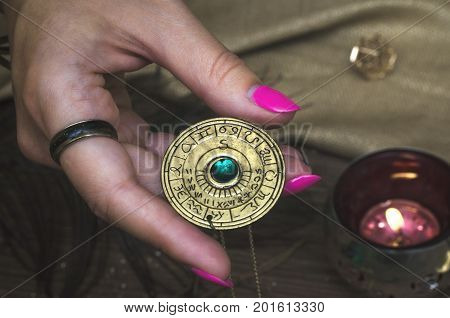 Amulet with zodiac signs in fortune teller hands. Divination. Witchcraft. Horoscope.