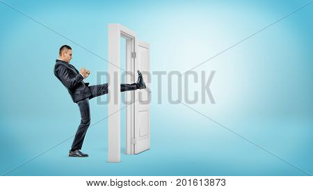A businessman in side view kicks a small white door open with his leg on blue backgrounds. Business and success. Opening all doors. Aggressive business approach.