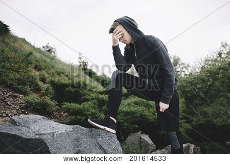 Well built runner is resting near the big stone. He has put his right leg on the stone and cover his face with his right arm. This guy is upset and tired of running so long.
