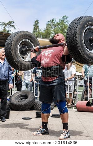 Almaty , Kazakhstan - May 28, 2017. strong man raises a heavy barbell. Weightlifting. City fesitwal sport on the street for a healthy lifestyle. Sports contests for arm-wrestling, heavy lifting, tug-of-war, army bench press