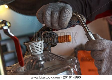hands with gloves repair car, changing the fluid in cars in service