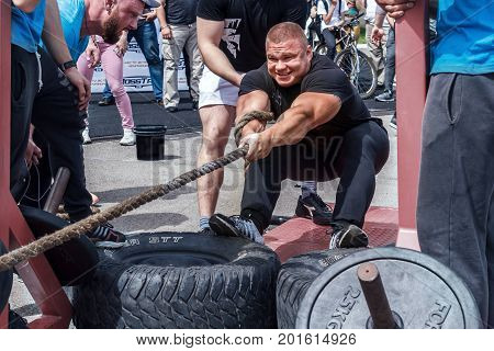 Almaty , Kazakhstan - May 28, 2017. Strong man pulls the rope. City fesitwal sport on the street for a healthy lifestyle. Sports contests for arm-wrestling, heavy lifting, tug-of-war, army bench press