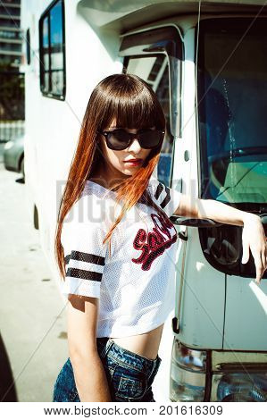 Portrait Attractive Women In Sports White T-shirt Against Background Of Camper Trailer, Transport Fo