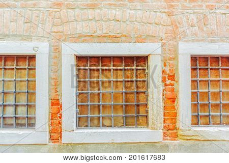 Three Windows In Old Town And Texture Of A Brick Wall Made From An Old Red Bricks. Picture Taken In