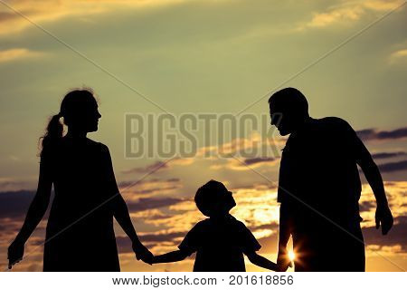 Happy Family Standing In The Park At The Sunset Time.