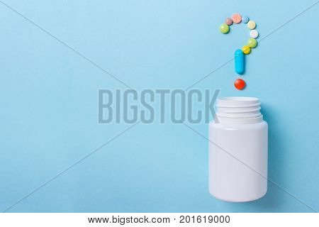 Assorted pharmaceutical medicine pills tablets and capsules symbol question mark on a blue background. Copy space for text
