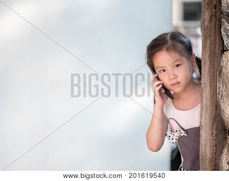 Asian girl hiding behind the wall use the smart phone