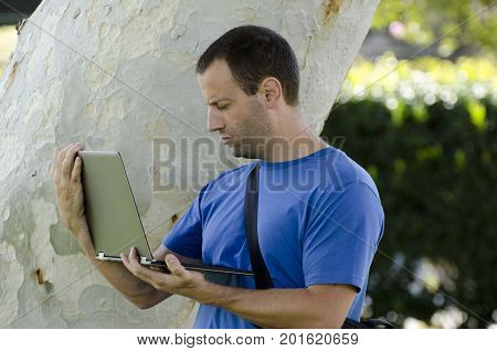 Man working on his lap top outside in front of a tree trunk.