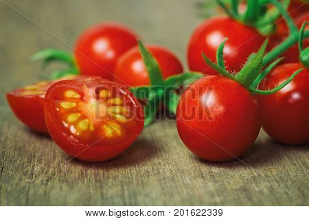 Fresh cherry tomato on rustic wood table. Close up lovely cherry tomato for background or wallpaper. Prepare fresh cut cherry tomato for home cooking look so delicious. Cut cherry tomato in macro concept with copy space.