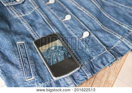 young start up small business owner use mobile phone to take photo of her product. freelance entrepreneur SME use smart phone to take picture and sell cloth on website. Online selling internet marketing e-commerce concept