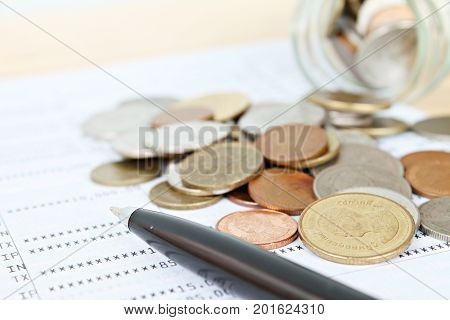 Business, finance, saving money, banking, loan, investment, taxes or accounting concept : Coins scattered from glass jar and pen on saving account book or financial statement