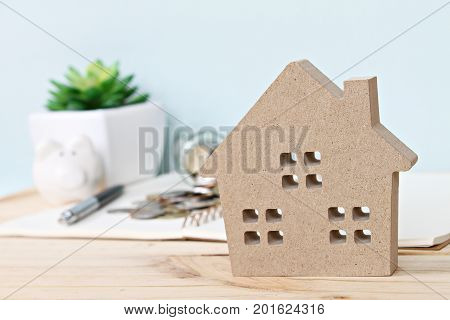 Business, finance, saving money, banking, property loan or mortgage concept : Wood house model in front of coins scattered from glass jar and piggy bank on wooden table