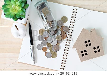 Business, finance, saving money, banking, property loan or mortgage concept : Top view or flat lay of wood house model, coins, open notebook paper and piggy bank on office desk table