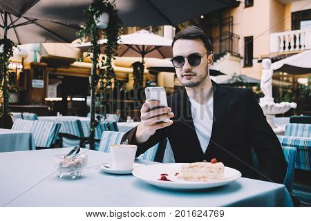 Young and ambitious businessman is sitting at the table in restaurant. He has his lunch on that table. The guy is looking to the phone and doing something on it. Close up