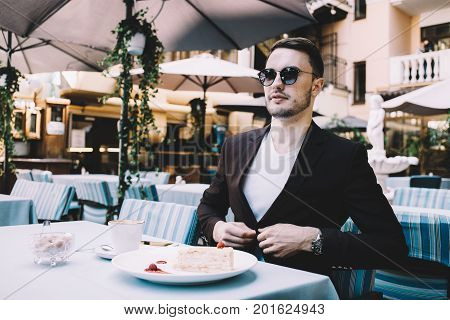The portrait of an ambitious businessman sitting at the table in a restaurant. He doesn't want to catch cold so that's why he is zipping the button on his jacket. Young man looks very confident. Close up