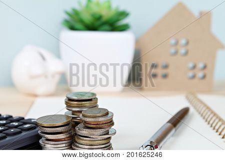 Business, finance, saving money, banking, property loan or mortgage concept : Coins stack and calculator in front of wood house model and piggy bank on office desk table