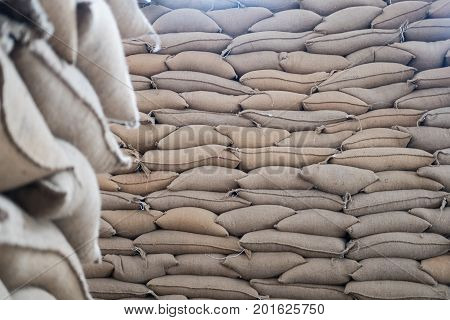 Hemp Sacks Containing Coffee Bean In Warehouse. Stacked Sacks In Storehouse.