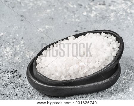 Granulated sugar in trendy plate with copy space. White sugar on gray concrete background. Copy space