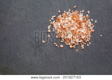 background of Himalayan salt - a heap of pink and orange coarse crystals on slate stone with a copy space